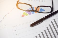 Pie chart and bar chart for analysis of sales. with pen and glas. Ses - business concept Stock Images