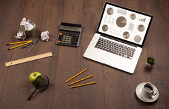 Pie chart graph icons on laptop screen with office accessories Royalty Free Stock Image