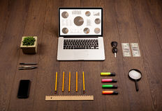 Pie chart graph icons on laptop screen with office accessories Stock Photography