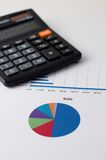 Pie chart with Sale headline and calculator. Vertical simple photo with color pie chart printed on paper sheet as main motif and with black calculator in Royalty Free Stock Photos
