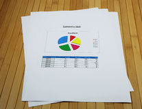 Pie chart is separated in the  paper on the bamboo desk Royalty Free Stock Photo