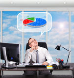 Pie chart. Young businessman sitting in office and dreaming on pie chart Royalty Free Stock Photography