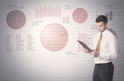 Pie charts and numbers on wall with salesman Royalty Free Stock Images