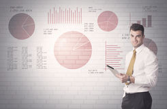 Pie charts and numbers on wall with salesman Royalty Free Stock Image