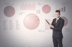 Pie charts and numbers on wall with salesman. Young sales business male in elegant suit standing in front of brick wall background with lines and pie charts Royalty Free Stock Photos