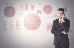 Pie charts and numbers on wall with salesman Stock Image