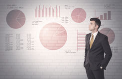Pie charts and numbers on wall with salesman. Young sales business male in elegant suit standing in front of brick wall background with lines and pie charts Royalty Free Stock Photography