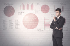 Pie charts and numbers on wall with salesman Stock Photography