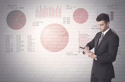 Pie charts and numbers on wall with salesman. Young sales business male in elegant suit standing in front of brick wall background with lines and pie charts Stock Image