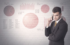 Pie charts and numbers on wall with salesman. Young sales business male in elegant suit standing in front of brick wall background with lines and pie charts Stock Photo