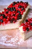 Pie cheesecake with berries on wooden plate. With sugar powder Stock Image