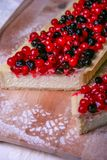 Pie cheesecake with berries on wooden plate. With sugar powder Royalty Free Stock Photography
