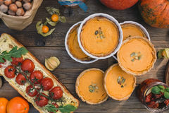 Pie with cherry tomatoes, pumpkin pie, orange and paper bag with nuts Stock Images