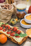 Pie with cherry tomatoes, pumpkin pie, orange and paper bag with nuts Royalty Free Stock Images
