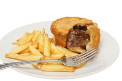 Pie and chips closeup. Closeup of steak pie and chips with a fork on a plate isolated against white stock images