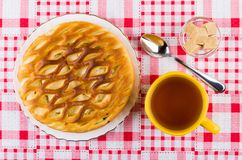 Pie with cottage cheese, cup of tea, sugar in bowl. Wicker pie with cottage cheese in plate, cup of tea, sugar in bowl and teaspoon on checkered tablecloth. Top Royalty Free Stock Photo