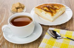 Pie with cottage cheese, cup with tea, sugar, teaspoon. Piece of pie with cottage cheese in plate, cup with tea on saucer, sugar, teaspoon on napkin on wooden Stock Images
