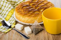 Pie with cottage cheese, empty cup, tea bag, sugar, teaspoon. Wicker pie with cottage cheese in plate, empty cup, tea bag, sugar and teaspoon on wooden table Royalty Free Stock Images