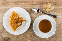 Pie with cottage cheese, tea, sugar in bowl and teaspoon. Piece of pie with cottage cheese in plate, cup with tea on saucer, sugar in bowl and teaspoon on wooden Stock Photos