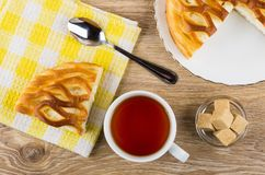 Pie with cottage cheese, teaspoon on napkin, tea, sugar. Piece of pie with cottage cheese, teaspoon on napkin, tea, sugar in bowl on wooden table. Top view Stock Images