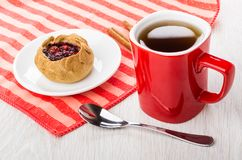 Pie with cowberries in saucer, cinnamon on napkin, tea, teaspoon. Pie with cowberries in saucer, cinnamon on striped napkin, cup of tea, teaspoon on wooden table Royalty Free Stock Photos