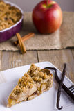 Pie with crumble on wooden background. Pie with crumble on plank background. Apple crumble. Apple pie with crumble on wooden background.A delicious piece of Stock Image
