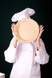 Pie Crust Faced. Assertive capture of a uniformed female Pastry Chef holding a finished pie crust in front of her face Stock Photo