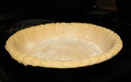 Pie Crust. On oven burner prior to baking Royalty Free Stock Photography