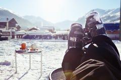 Pie de botas de esquiar que llevan de un esquiador, resto de la sentada y el tener en un café fotos de archivo libres de regalías