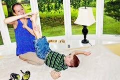 Pie de elevación del niño a la muchacha a las cosquillas imagen de archivo libre de regalías