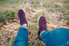 Pie de la mujer con el zapato y la mezclilla azul que se sientan solamente encima del MES imagen de archivo libre de regalías