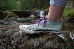 Pie de las muchachas que camina en una roca cubierta de musgo Imágenes de archivo libres de regalías