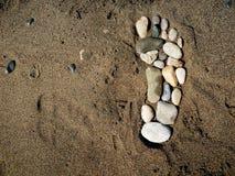 Pie de piedra en la arena Foto de archivo libre de regalías