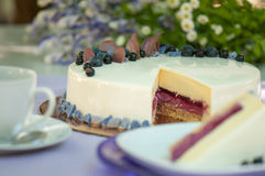 Pie decorated with fresh berries. Against a flowers Royalty Free Stock Photography