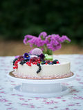 Pie decorated with fresh berries. Against a flowers and macarons Royalty Free Stock Images