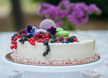 Pie decorated with fresh berries. Against a flowers and macarons Stock Photo