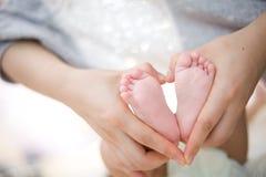 Pie del bebé como dimensión de una variable del corazón del amor Foto de archivo libre de regalías
