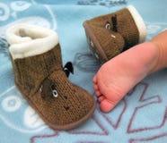 Pie del bebé en el fondo de las botas de lana Imágenes de archivo libres de regalías