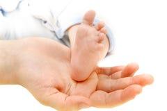 Pie del bebé en la mano de los padres Fotos de archivo libres de regalías