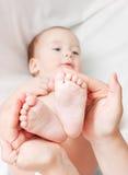 Pie del bebé en las manos de la madre Foto de archivo libre de regalías