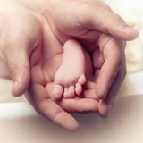 Pie del bebé en manos del varón adulto. Imagen de archivo