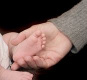 Pie del bebé en una mano del adulto Foto de archivo libre de regalías
