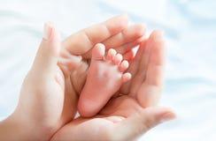 Pie del bebé en manos de la madre Foto de archivo libre de regalías
