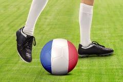 Pie del futbolista que juega la bola en el campo Imágenes de archivo libres de regalías