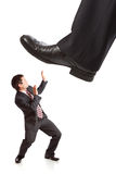 Pie del hombre de negocios que camina en hombre de negocios minúsculo Imagenes de archivo