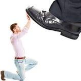 Pie del hombre de negocios que camina en hombre de negocios minúsculo Imagen de archivo libre de regalías