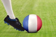 Pie del jugador de fútbol que golpea la bola con el pie en el campo Imagenes de archivo