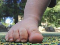 Pie del muchacho sobre el piso de goma Imagen de archivo