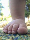 Pie del muchacho sobre el piso de goma Foto de archivo