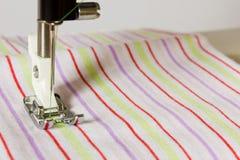 Pie del primer de la máquina de coser en un paño rayado Foto de archivo libre de regalías